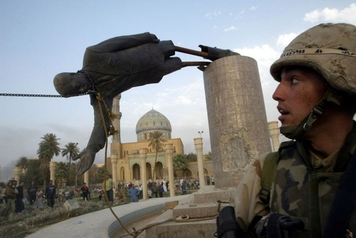 U.S. Marine Kirk Dalrymple watches as a statue of Iraq's President Saddam Hussein falls in central Baghdad. [2003] Source: Reuters