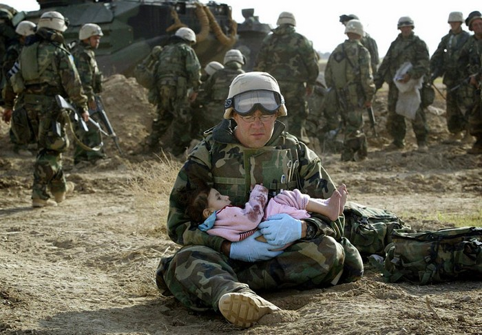 U.S. Navy Hospital Corpsman HM1 Richard Barnett, assigned to the 1st Marine Division, holds a child after she was separated from her family during a firefight [2003] Source: Damir Sagolj