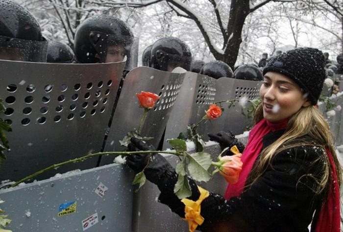 A Ukrainian woman places carnations into shields of anti-riot policemen standing outside the presidential office in Kiev. Ukraine, during the 2004 Orange Revolution. [2004] Source: Vasily Fedosenko
