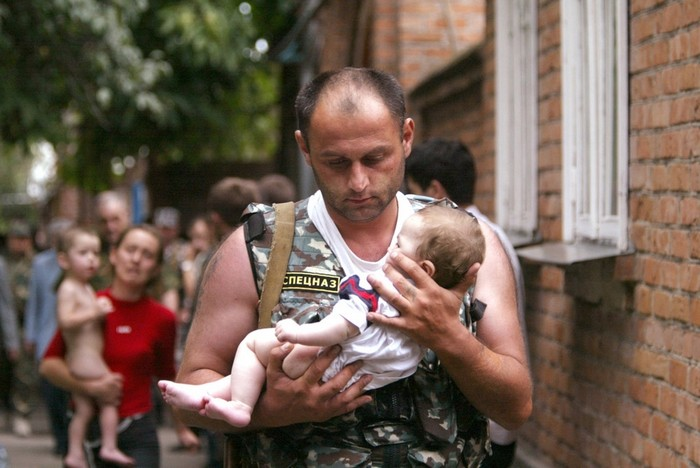 A Russian police officer carries a released baby from the school seized by heavily armed masked men and women in the town of Beslan. [2004] Source: Victor Korotayev