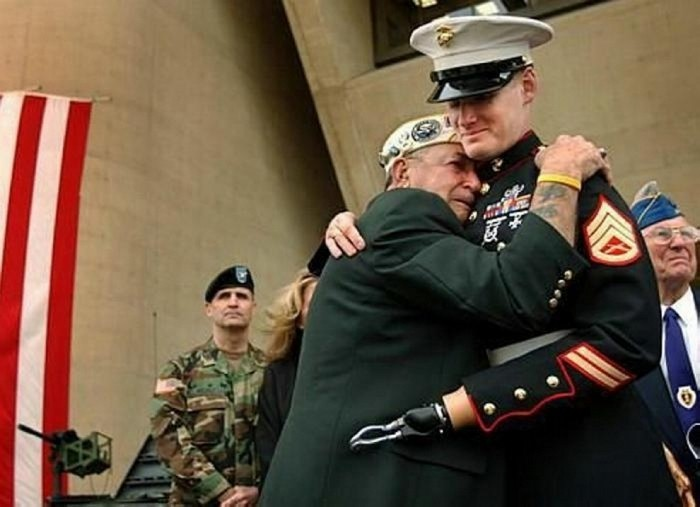 Pearl Harbor survivor Houston James of Dallas embraces Marine Staff Sgt. Mark Graunke Jr. who lost a hand, leg, and eye while defusing a bomb in Iraq. [2005] Source: Dallas Morning News