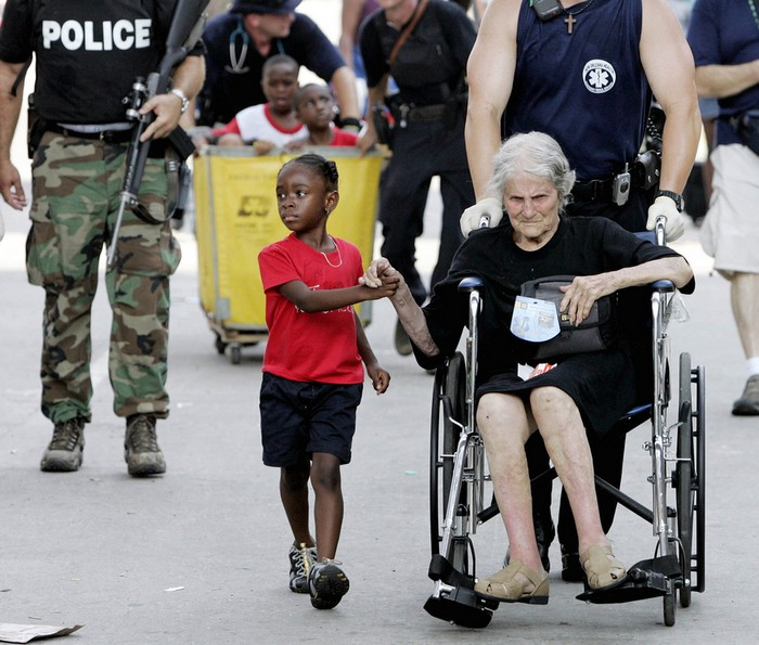 Tanisha Blevin, 5, holds the hand of fellow Hurricane Katrina victim Nita LaGarde, 105, as they are evacuated from the convention center in New Orleans. [2005] Source: Eric Gay