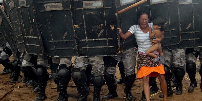 An indigenous woman holds her child while trying to resist the advance of Amazonas state policemen in Manaus who have been sent to evict natives. [2008] Source: Luiz Vasconcelos