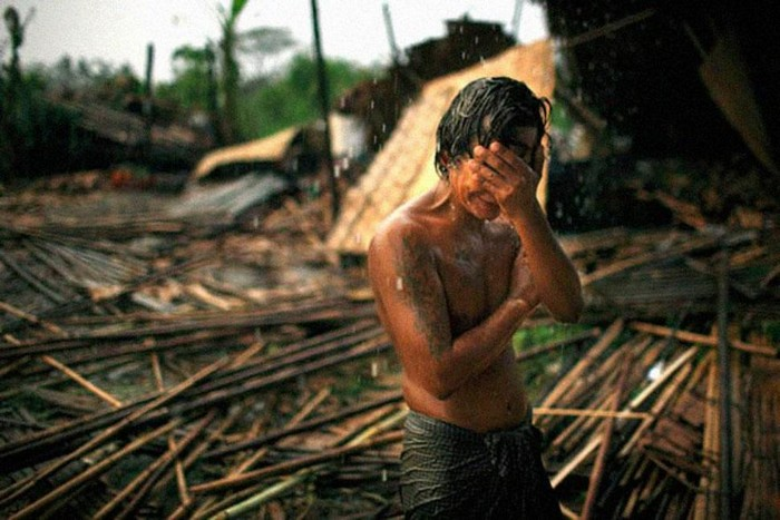 Hhaing The Yu, 29, holds his face in his hand as rain falls on the decimated remains of his home after a cyclone stroke Myanmar's capital of Yangon. [2008] Source: Brian Sokol