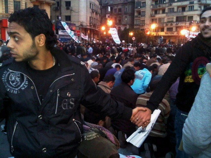 Christians protect Muslims in prayer at Tahrir Square during the Egyptian Revolution [2011] Source: Nevin Zaki