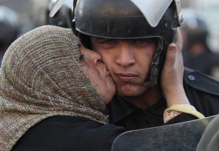 An Egyptian woman kisses a policeman, who had refused to fire on protestors, during the revolution against the Mubarak Government [2011] Source: Unknown Photographer