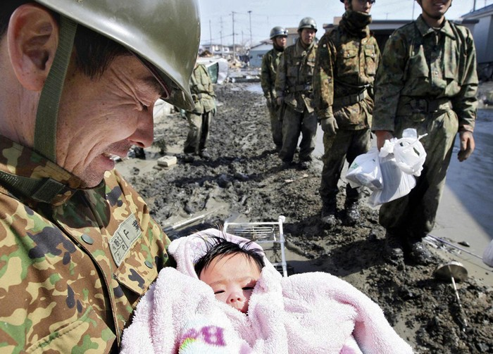 A 4-month-old baby girl is rescued from the rubble four days after the Japanese tsunami. [2011] Source: Reuters