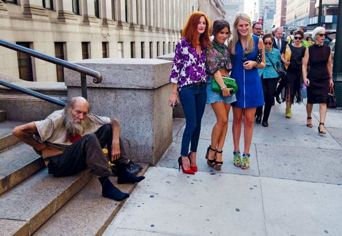 Three young women from the New York Fashion Week pose next to a homeless man. [2012] Source: Spiegel