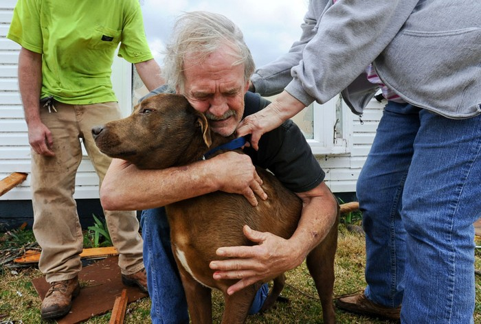 Greg Cook hugs his dog Coco after finding her inside his destroyed home in Alabama following the Tornado. [2012] Source: The Decatur Daily