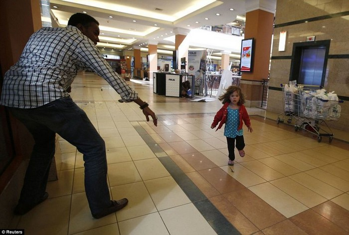 A child runs to safety as armed police hunt gunmen who went on a shooting spree at Westgate shopping centre in Nairobi. [2013] Source: Reuters