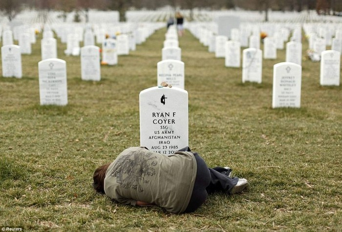 Lesleigh Coyer, 25, of Saginaw, Michigan, lies down in front of the grave of her brother, Ryan, who served with the U.S. Army in both Iraq and Afghanistan [2013] Source: Reuters